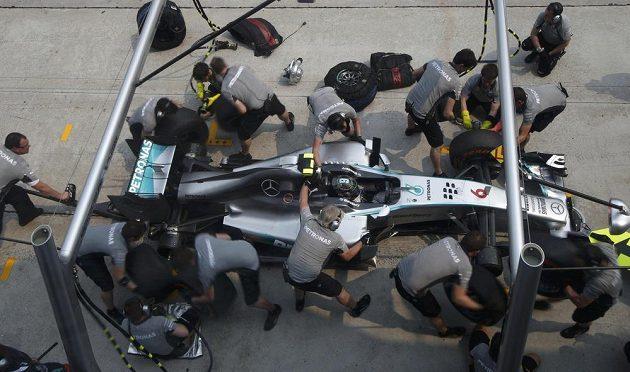 Mechanici Mercedesu mění gumy na voze Nika Rosberga při měřeném tréninku v Sepangu.