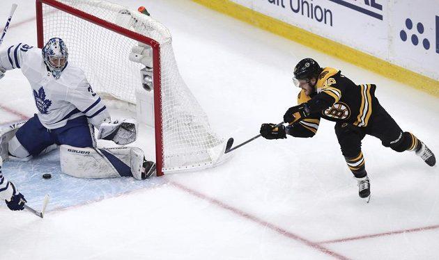 Hokejový útočník Bostonu Bruins David Pastrňák zkouší překvapit v play off NHL brankáře Toronta.
