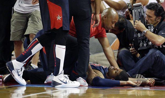 Paul George leží na palubovce bezprostředně poté, co si zlomil nohu.