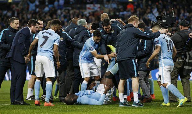 Ležící zraněný Yaya Toure z Manchesteru City se spoluhráči po úspěchu v penaltovém rozstřelu s Liverpoolem.