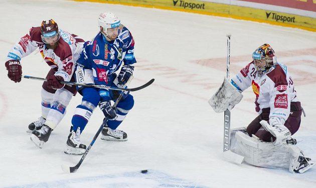 Brankář Sparty Tomáš Pöpperle zasahuje během čtvrtfinále play off hokejové extraligy s Kometou Brno. Zleva obránce Sparty Jan Piskáček atakuje útočníka Komety Hynka Zohoru.