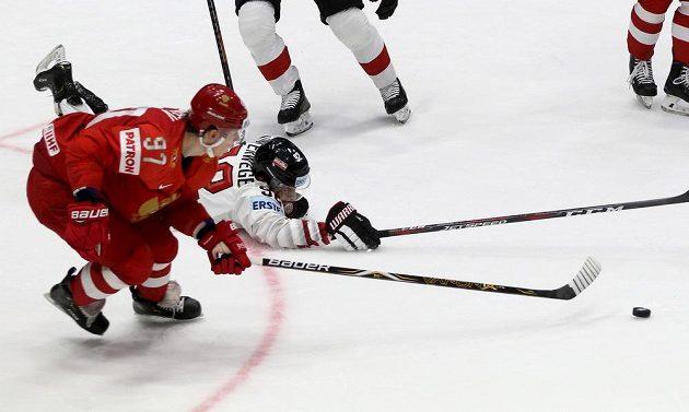 Ruský hokejista Nikita Gusev v souboji s Rakušanem Clemensem Unterwegerem v utkání mistrovství světa.