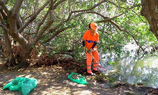 V padesátimetrových rozestupech uklízející pracovníci hygienické služby břehy jezera, kam voda vyplavuje další a další leklé ryby.
