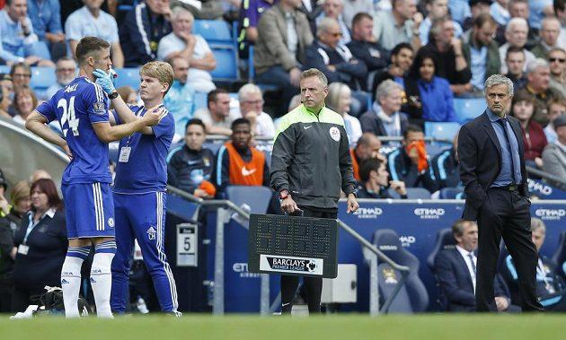 Lékař Chelsea Chris Hughes ošetřuje zraněného Garyho Cahilla pod přísným dozorem Josého Mourinha.