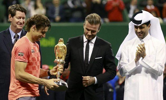 Bývalý anglický fotbalový reprezentant David Beckham předává Davidu Ferrerovi trofej pro vítěze turnaje v Dauhá.
