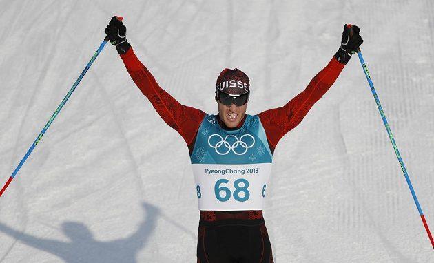 Švýcar Dario Cologna se raduje ze třetího triumfu za sebou v olympijském závodě závodě na 15 km.