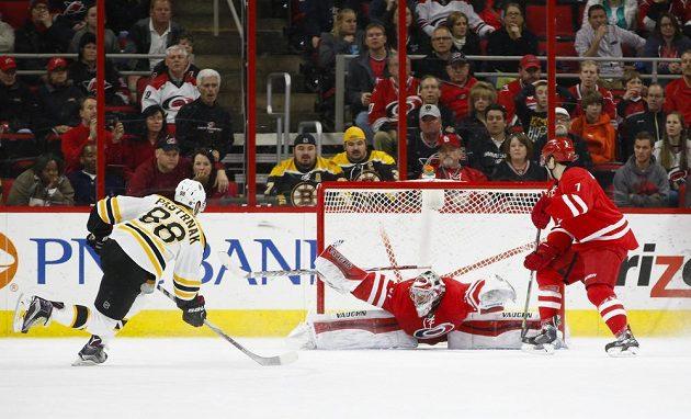 David Pastrňák střílí v prodloužení zápasu s Carolinou brankáři Antonu Chudobinovi vítězný gól Bostonu.