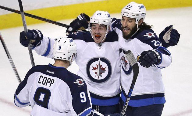 Hokejisté Winnipegu Jets Nicolas Petan (19) Chris Thorburn (22) a Andrew Copp (9) se radují z gólu proti Bostonu.