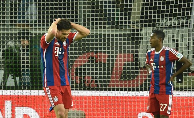 Zklamaný záložník Bayernu Mnichov Xabi Alonso (vlevo) a obránce David Alaba po porážce ve Wolfsburgu.