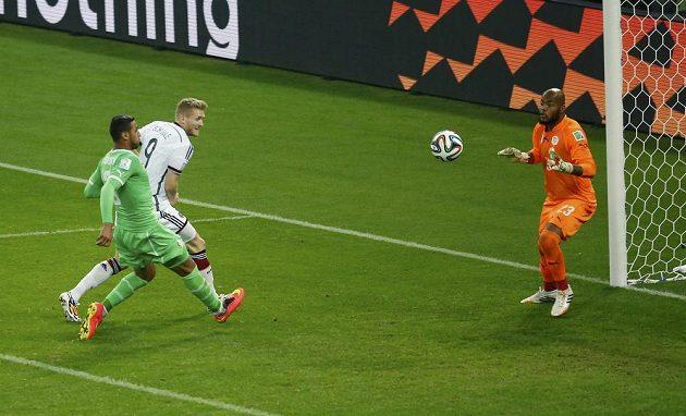 Německý fotbalista André Schürrle (v bílém dresu) střílí gól alžírskému brankáři Raísovi Mbulhimu.