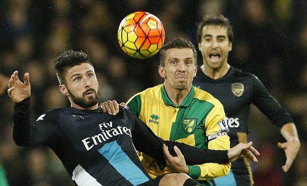 Olivier Giroud z Arsenalu (vlevo) a v pozadí jeho spoluhráč Mathieu Flamini v souboji s Gary O'Neilem z Norwiche.