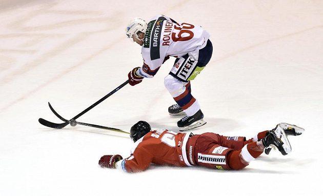 Olomoucký obránce Robin Staněk se vleže snaží vypíchnou puk z hokejky pardubického útočníka Tomáše Rolinka.