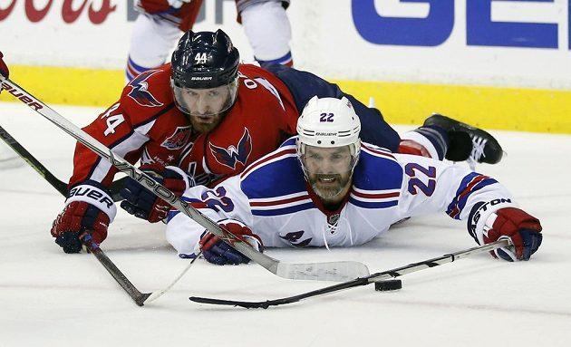 Obránce Washingtonu Brooks Orpik (vlevo) a zadák Dan Boyle z New York Rangers v nezvyklém souboji vleže na ledě.