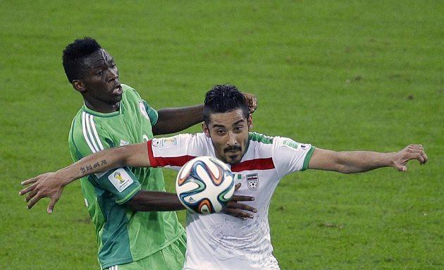 Íránský útočník Rezá Ghúčanedžhád bojuje o míč s nigérijským obráncem Kunlem Odunlamim (vlevo).