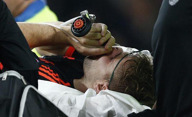 Luke Shaw z Manchesteru United opouští hřiště v Eindhovenu s kyslíkovou maskou.