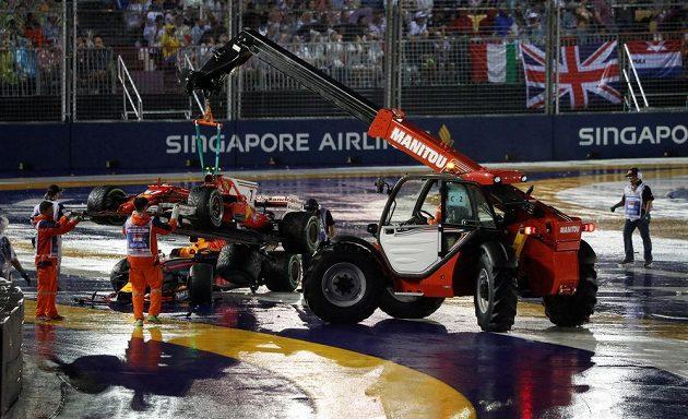 Jeřáb uklízí po startu Velké ceny Singapuru monoposty Kimiho Räikkönenena, Maxe Verstappena a Sebastiana Vettela.