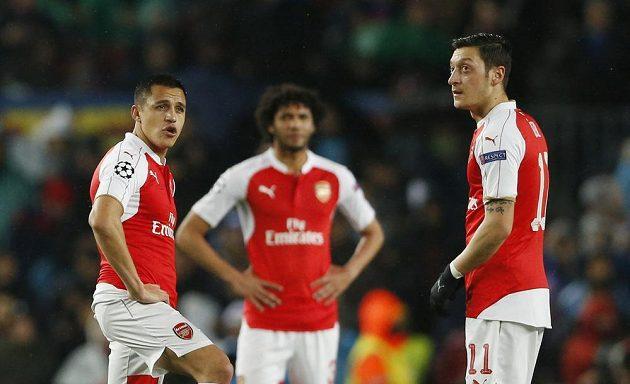 Fotbalisté Arsenalu Alexis Sánchez (vlevo) a Mesut Özil rozehrávají na stadiónu Barcelony po inkasovaném gólu