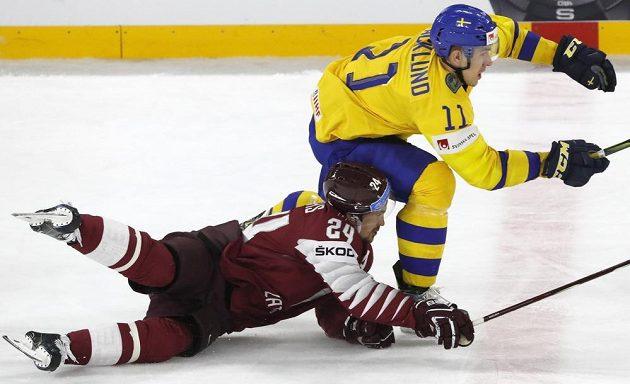 Mikelis Redlihs stíhá švédského útočníka Mikaela Backlunda.