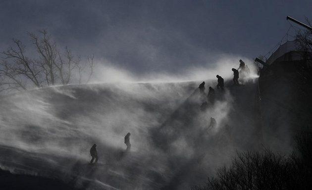 Četa dobrovolníků v těžkých podmínkách odloženého obřího slalomu žen.