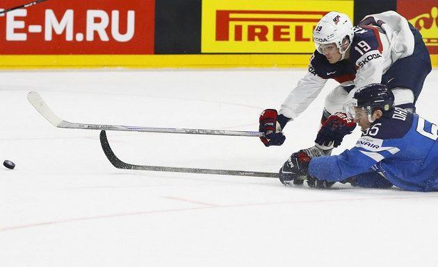 Americký hokejista Clayton Keller se natahuje za pukem, touš se snaží během čtvrtfinále mistrovství světa zasáhnout i Fin Atte Ohtamaa.