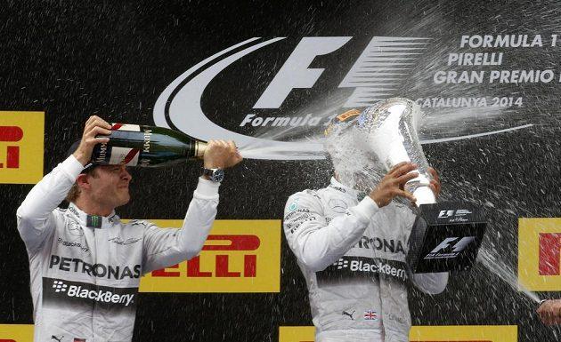 Vítěz Lewis Hamilton (vpravo) s trofejí v tříšti šampaňského, jímž stájového kolegu kropí v pořadí druhý Nico Rosberg.