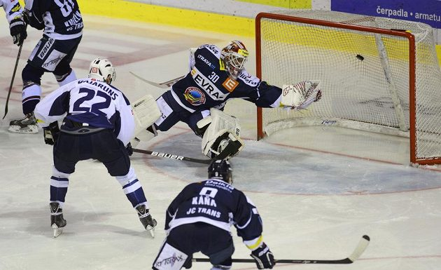 Kladenský forvard Lauris Bajaruns (vlevo) překonává vítkovického brankáře Daniela Dolejše v utkání 29. kola hokejové Tipsport extraligy.