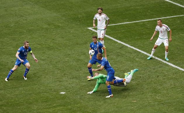 Maďarský brankář Gábor Király (v zeleném dresu) chyboval, neudržel centr a po následném závaru byl nařízen pokutový kop pro Islanďany. S gólmanem o míč bojuje Ragnar Sigurdsson (6).