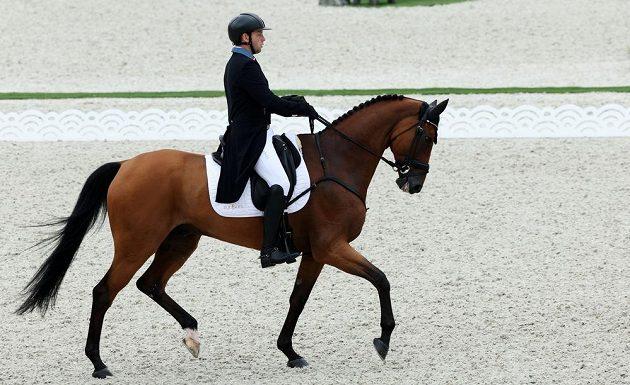 Český jezdec Miloslav Příhoda vede koně Ferreoluseho v olympijské soutěži ve všestrannosti