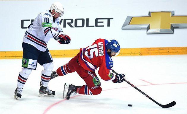 Sergej Mozjakin z Magnitogorsku (vlevo) a Justin Azevedo ze Lva Praha bojují o puk během utkání finále play off KHL.