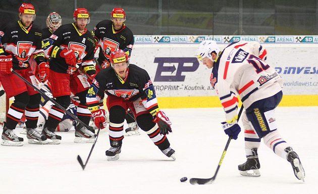 Hokejisté Hradce Králové se snaží zablokovat střelu chomutovského forvarda Davida Kämpfa.
