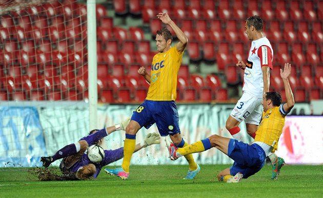 David Jablonský z Teplic (uprostřed) tečuje míč před slávistickým brankářem Radkem Černým a střílí gól.