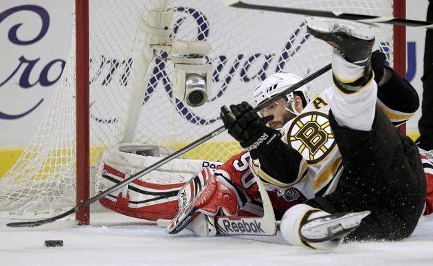 Patrice Bergeron z Bostonu se snaží v akrobatické pozici vyzrát na Coreyho Crawforda v brance Chicaga v úvodním finále Stanley Cupu.