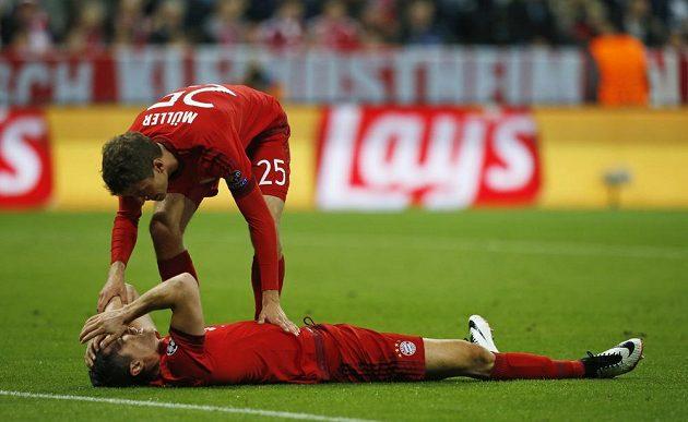 Robert Lewandowski leží na trávníku po neproměněné šanci v odvetě semifinále Ligy mistrů proti Atlétiku Madrid. Nad ním stojí Thomas Müller.