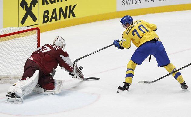 Švédský hokejista Dennis Rasmussen se snaží překonat gólmana Lotyšska Kristerse Gudlevskise.