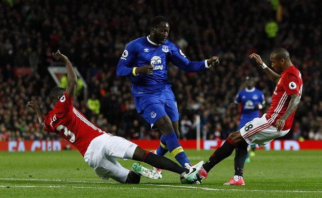Útočník Evertonu Romelu Lukaku v akci během utkání Premier League na hřišti Manchesteru United. Snaží se ho zastavit dva soupeři.