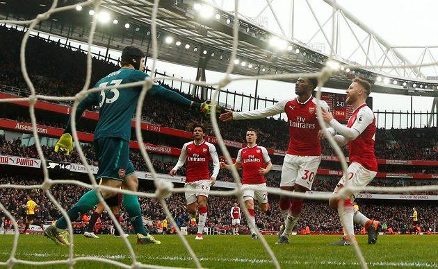Spoluhráči gratulují Petru Čechovi z Arsenalu k chycenému pokutovému kopu.
