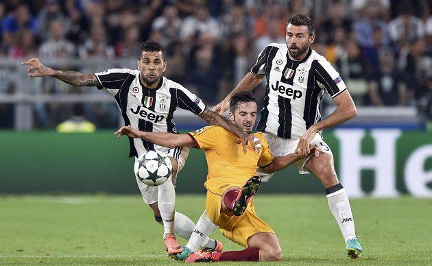 Hráči Juventusu Dani Alves a Andrea Barzagli a proti nim Paolo Sarabia ze Sevilly.