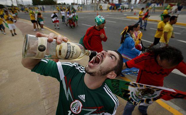 Fanoušek Mexika slaví úspěch svého týmu s lahví tequily.
