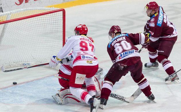 Sparťan Tomáš Rolinek (uprostřed) překonává brankáře Třince Šimona Hrubce.