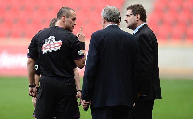 Rozhodčí Miroslav Zelinka (vlevo) reší s hlavním pořadatelem a delegátem pokřiky fanoušků Slavie během utkání s Jabloncem.