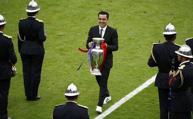 Španělský fotbalista Xavi přináší trofej pro nové mistry Evropy před začátkem finále.