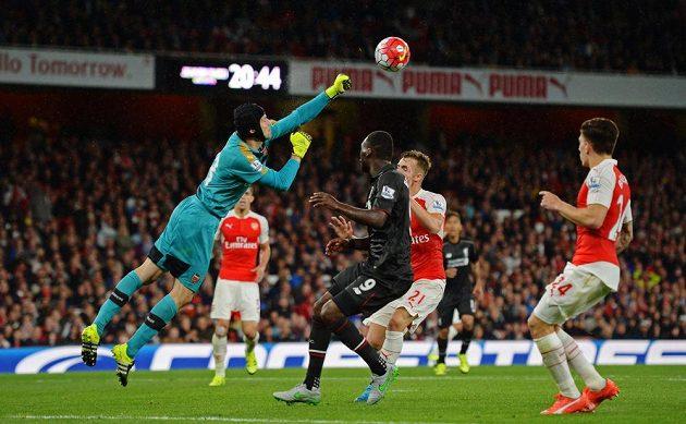 Petr Čech v bráně Arsenalu zasahuje před liverpoolským Christianem Bentekem.