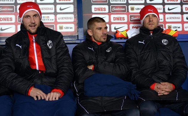 Plzeňský záložník Jan Rezek (uprostřed) sedí na lavičce náhradníků během utkání proti Spartě. Vlevo je obránce Plzně Roman Hubník, vpravo útočník Marek Bakoš.