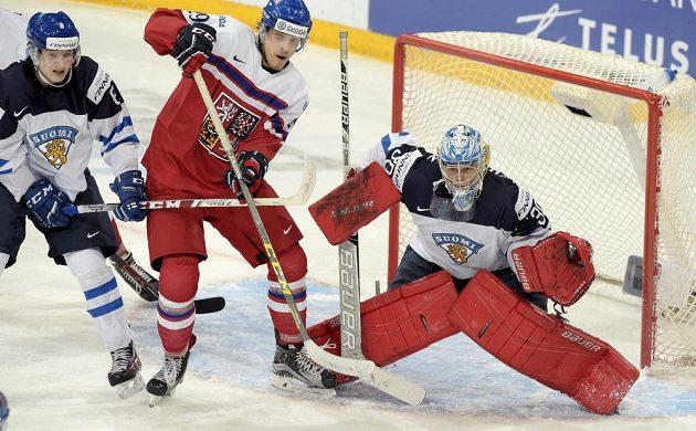 Český hokejista Jiří Smejkal (uprostřed) před finským gólmanem Veini Vehvilainenem. Zleva dotírá Joni Tuulola.