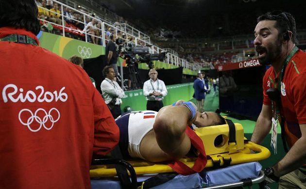 Zraněného francouzského gymnastu Samira Aita Saida odnášejí na nosítkách.