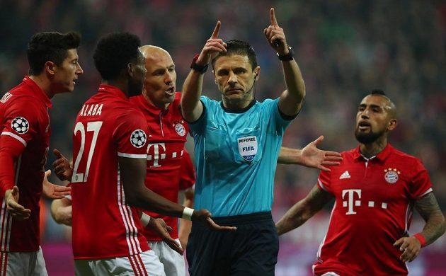 Fotbalisté Bayernu diskutují s rozhodčím po odpískaní přísné penalty ve prospěch Arsenalu.