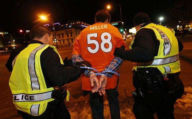 Denverská policie odvádí jednoho z fanoušků, který to přehnal se slavením triumfu Bronchos ve finále ligy amerického fotbalu NFL.