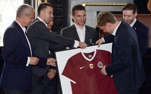 Pražský primátor Tomáš Hudeček (vpravo) dostává od zástupců Sparty podepsaný dres.