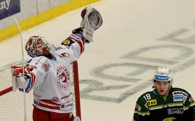 Třinecký brankář Šimon Hrubec slaví vítězství nad Karlovými Vary. Vpravo je útočník Energie Vojtěch Tomeček.