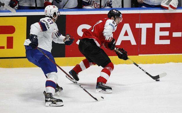 Norský hokejista Andreas Martinsen a Rakušan Konstantin Komarek v akci během utkání mistrovství světa.